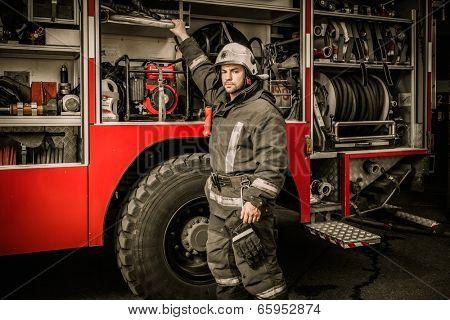 Fireman taking equipment from firefighting truck