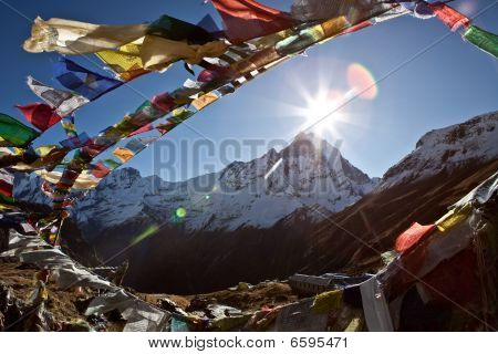 Buddhist prayer flags above Mt. Annapurna Base Camp, at 4.200 mt. of altitude. The mountain is possible to notice in the middle of the flags round is the Machhapuchhare, which is 6993 metres high. poster