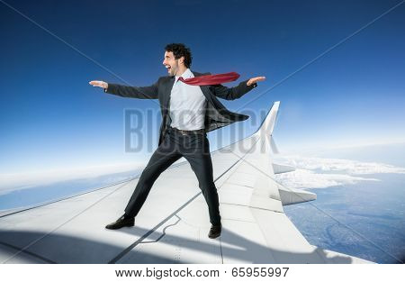 Fearless businessman riding an airplane