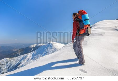 Hiker girl with backpack  in a high mountains