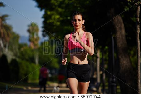 Female jogger in the sportwear running in the green park