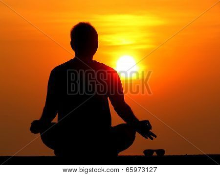 A Man Keeping Aside His Sunglasses Aside And Meditating On The Rising Sun On A Spiritual Holiday