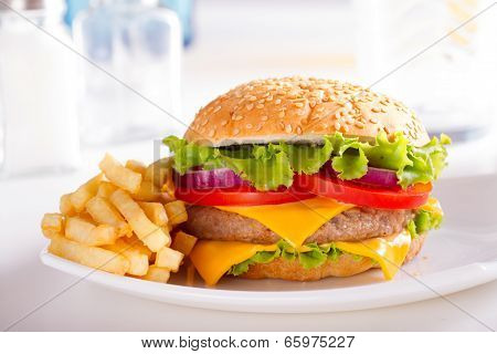 Classic fast food. Mouthwatering french fries and burger. Delicious burger with french fries. Burger and fries on kitchen table. Homemade burger and french fries in morning light. Classic burger or hamburger on kitchen background. Fast food ads.