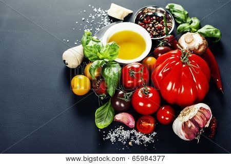 Fresh grape tomatoes with basil and vegetables on a dark background