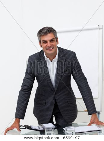 Charming Businessman Leaning On A Conference Table