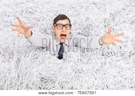 Terrified young man drowning in a pile of shredded paper