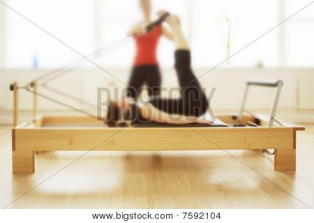 Pilates apparatus in use by two women, soft focus