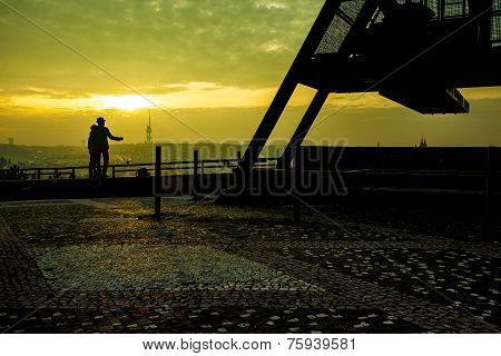 Lovers Standing At The Prague Metronome At Sunrise