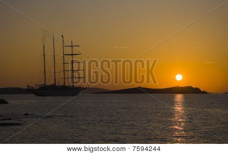 A Silhouette Of A Sailing Yacht On An Orange Sunset