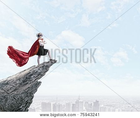 Cute girl of school age in superhero costume