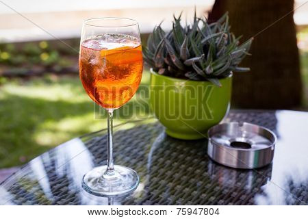 Glass Of Aperol Spritz With Ashtray And Cactus