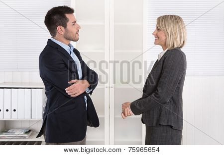 Business people in suit and dress talking together: small talk.