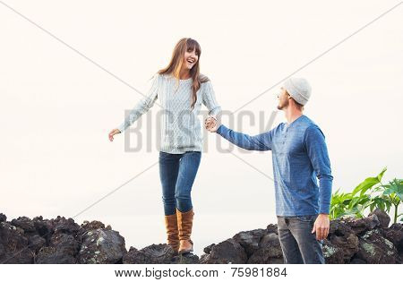 Happy Young Couple Having Fun Outdoors. Man helping attractive girlfriend over rock wall. Chivalry Concept, Romantic Date.