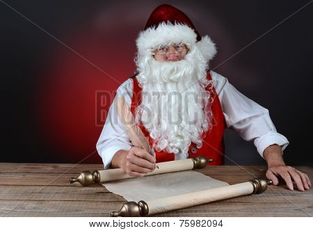 Santa Claus making his naught and nice list on a scroll of parchment paper. Santa is seated at a rustic wood table. Horizontal format on light to dark red background.