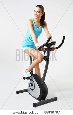 Spinning woman exercising on a stationary bike