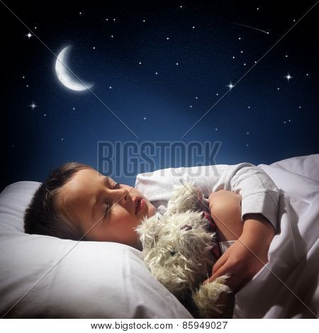 Child sleeping and dreaming in his bed under the moon, stars and blue night sky
