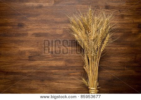 Wheat Ears on the Wooden Table. Sheaf of Wheat over Wooden. Harvest concept