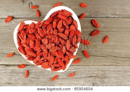 Heart shaped bowl of goji berries on wood