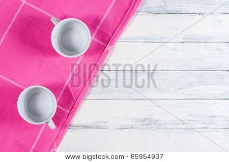 Two coffee cups on pink dishtowel and white wood background