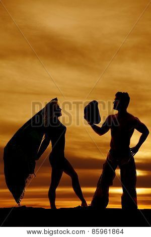 A silhouette of a woman holding her sarong in the air with the wind blowing. Her cowboy taking off his hat for her. poster