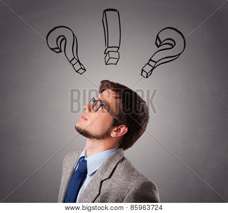 Young man standing and thinking with question marks overhead