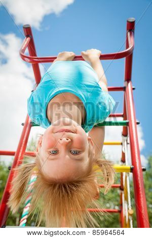 Portrait of cute blond girl with blue eyes wearing blue tshirt sitting on monkey bars on a summer day. Girl looking at camera smiling. Green leaves a seen in the background.