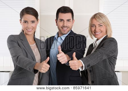 Thumbs up: three successful business people of man and woman in a team.