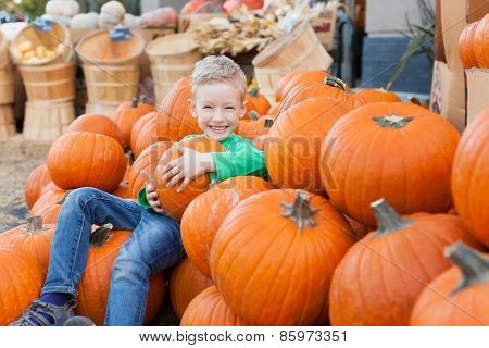 little excited kid enjoying time at pumpkin patch sitting in the huge pile of pumpkins poster