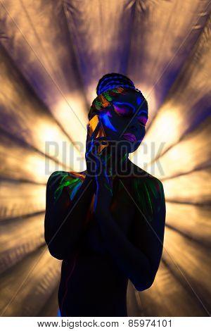 Sexy go-go dancer posing under ultraviolet light
