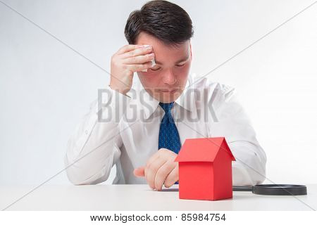 Sad Man with a magnifying glass and paper house