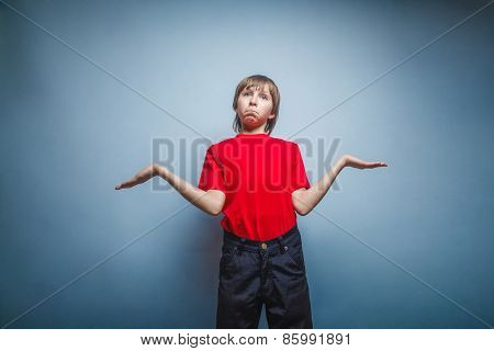 Boy, teenager, twelve years in red T-shirt, threw up his hands,