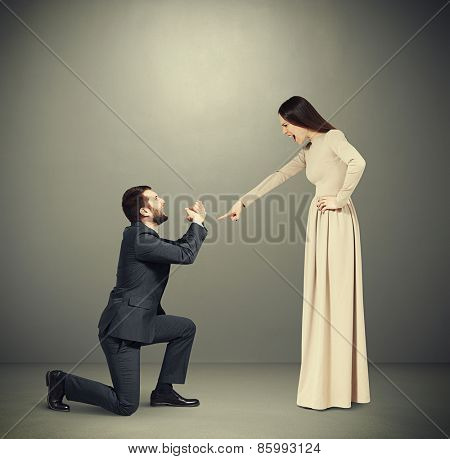 full length portrait of emotional couple over grey background. angry woman pointing and screaming at man, man standing on knee and apologizing