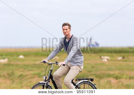Man having bicycle tour with bike at levee with sheep