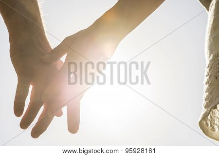 Romantic Couple With Clasped Hands Backlit By A Bright Evening Sun