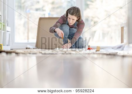 Young Woman Assembling A Diy Furniture At Home Kneeling On The Floor In Front Of A Bright Glass Wind