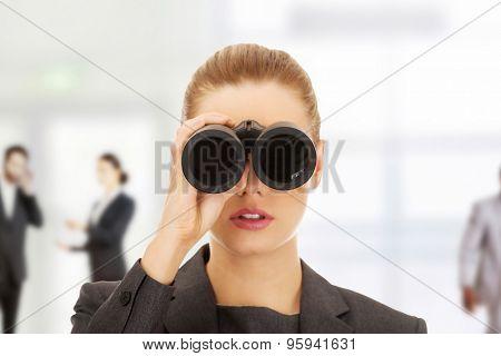 Caucasian businesswoman looking through binoculars.