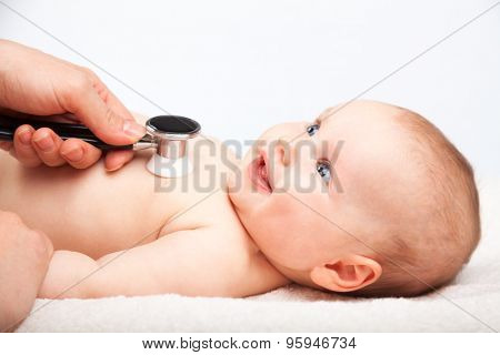 Pediatrician examines three month baby girl. Doctor using a stethoscope to listen to baby's chest checking heart beat. Child is looking at a doctor