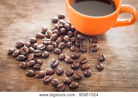 Coffee Beans With Coffee Cup On Wooden Table