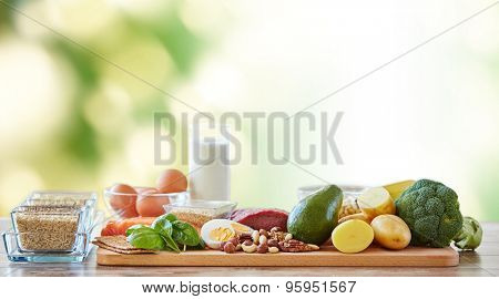 balanced diet, cooking, culinary and food concept - close up of vegetables, fruits and meat on wooden table over green natural background