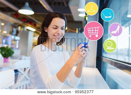people, online shopping, technology and lifestyle concept - smiling young woman with smartphone and internet icons at cafe