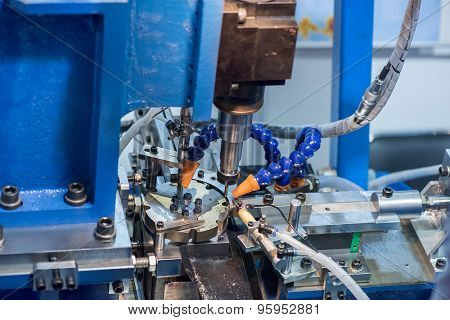 cnc metal working machine with cutter tool during metal detail milling at factory