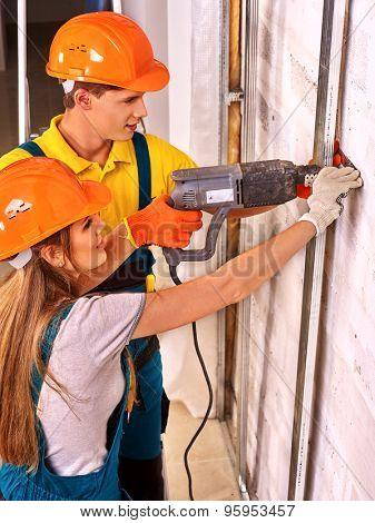 Happy woman working  and man in builder uniform indoor.