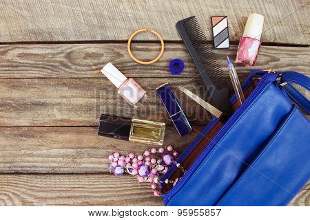 Things from open lady handbag. women's purse on wood background. Cosmetics and women's accessories