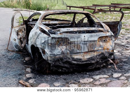 Burnt out rusted old car near the road
