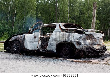 Burnt out rusted old car near the road and forest