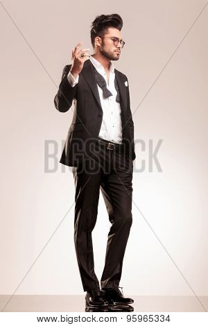 Full length picture of a handsome business man holding his right hand up while looking away from the camera.