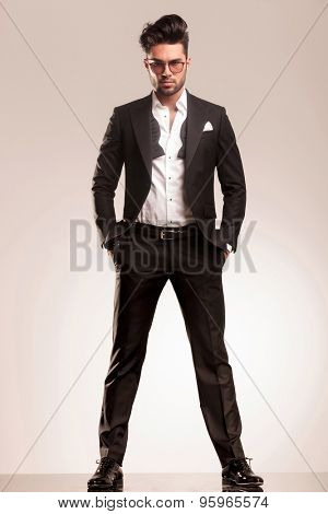 Attractive young business man looking at the camera while standing with both hands in his pocket.