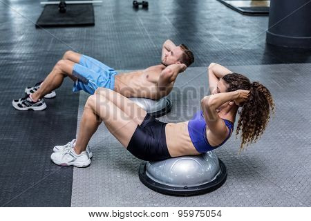 Muscular couple doing bosu ball exercises at the crossfit gym