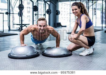 Portrait of a muscular man doing bosu ball push ups