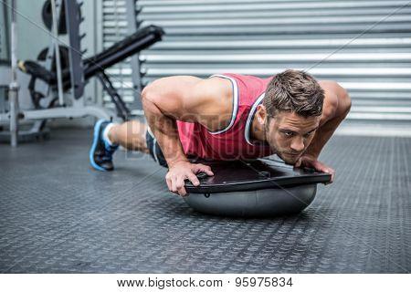Muscular man using bosu ball in crossfit gym